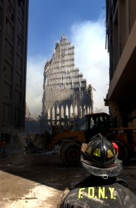010913-N-1350W-003 New York, N.Y. (Sept. 13, 2001) -- A New York City fire fighter looks up at what remains of the World Trade Center after its collapse following a Sept. 11 terrorist attack. U.S. Navy Photo by Photographer's Mate 2nd Class Jim Watson. (RELEASED)